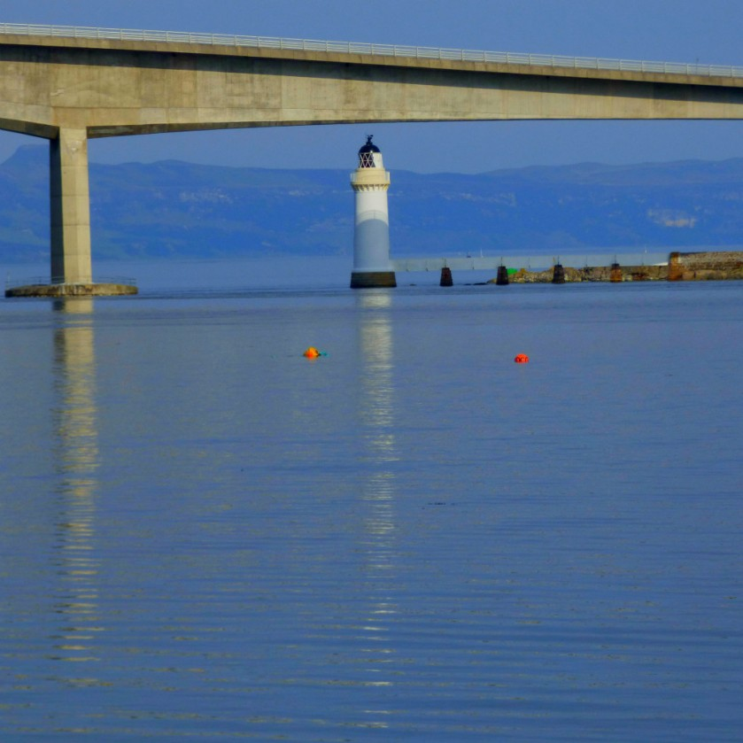 Lighthouse below bridge